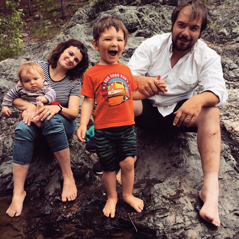 young family hangs out together in nature barefooted