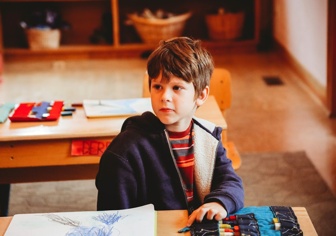 first grade boy sitting in classroom with coloring crayons and paper