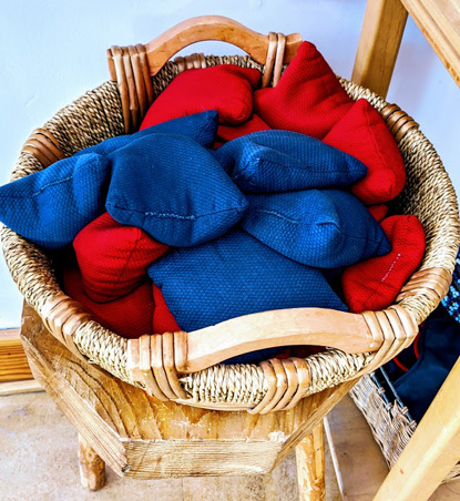 whicker basket full of hand-sewen red and blue bean bags